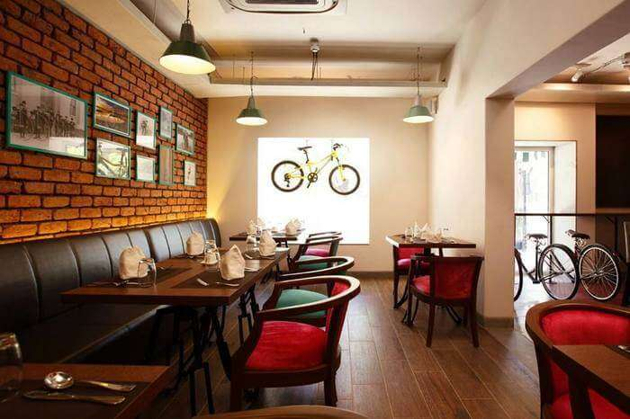 A cycle hung on Mushroom Cafe window Alleppey, Red colour chairs with wooden tables at Mushroom Cafe
