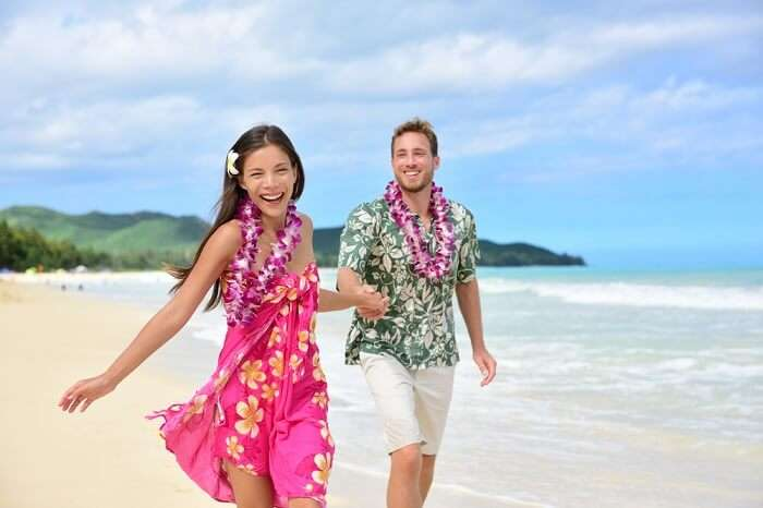 Happy couple having fun on Hawaii beach wearing Aloha shirt and pink sarong sun dress and flower leis