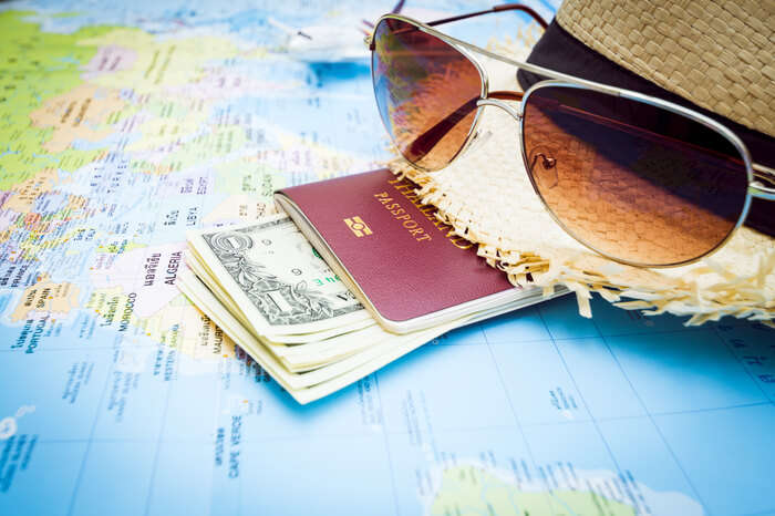 passport currency notes and sunglasses on a world map