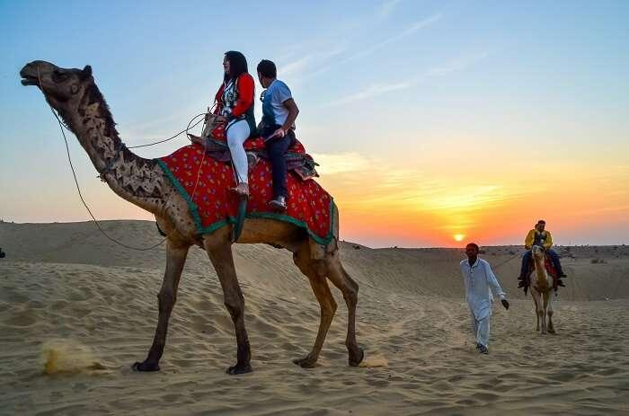 couple enjoying desert camel safari in Jaisalmer, India