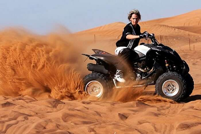 Traveler taking up dune bashing during desert safari in Dubai