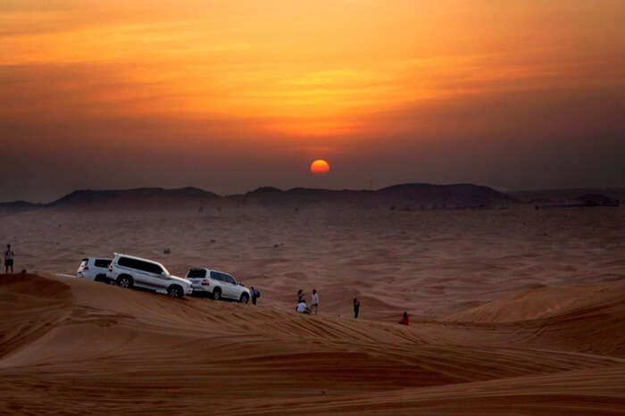 Travelers watching sunrise during desert safari in Dubai
