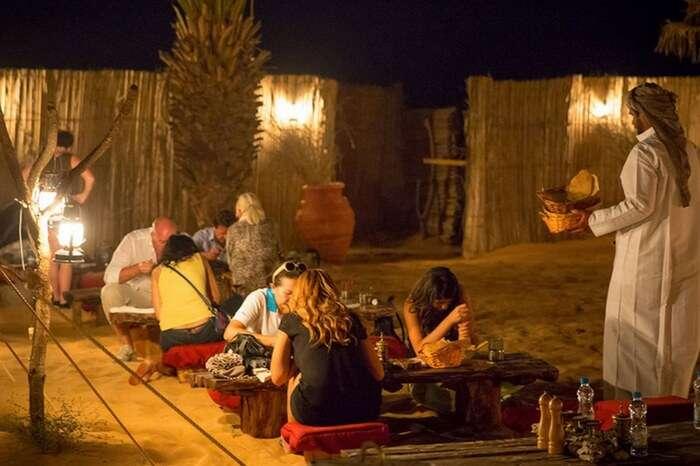 Travelers enjoying buffet dinner during desert safari in Dubai