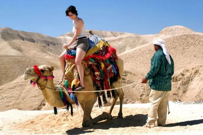 A tourist riding a camel during desert safari in Dubai