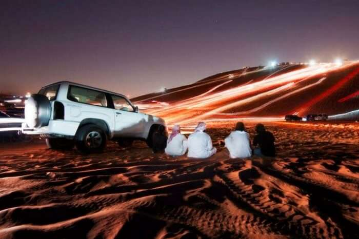 Travelers enjoying a night safari in Arabian desert in Dubai