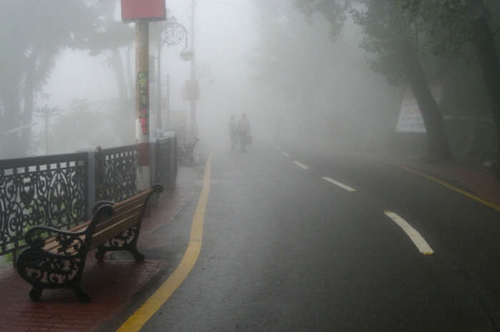 People walking past the Mall Road in Mussoorie on a foggy day