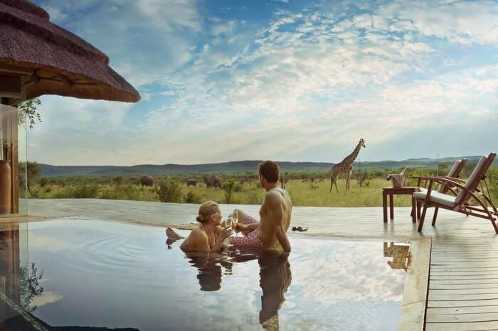 Couple spending romantic moments in a pool during safari honeymoon in South Africa