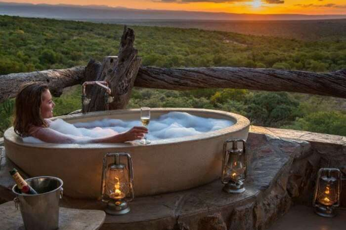 A honeymooner showering in a tub in jungle lodge in South Africa