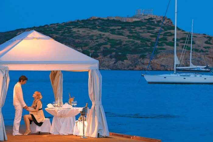 Couple during a romantic dining by the sea in Athens in Greece