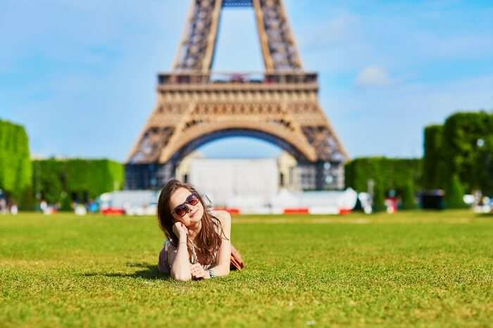 a girl posing near Eiffel Tower Paris
