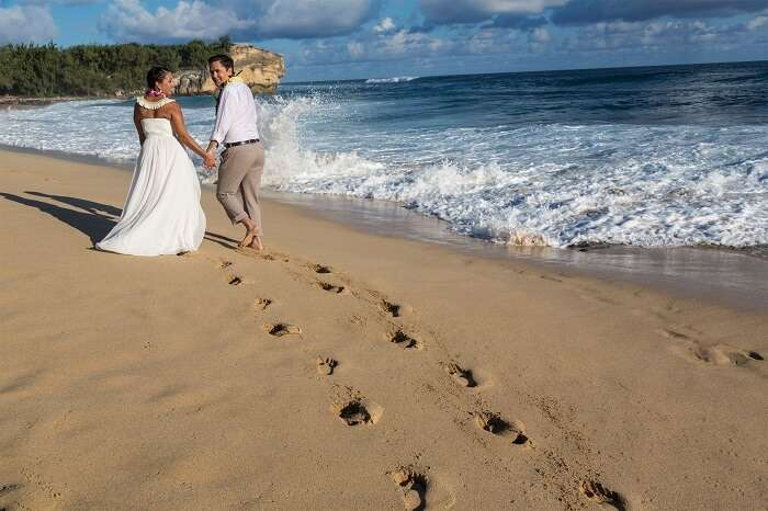 romantic couple walking on the beach in Kauai