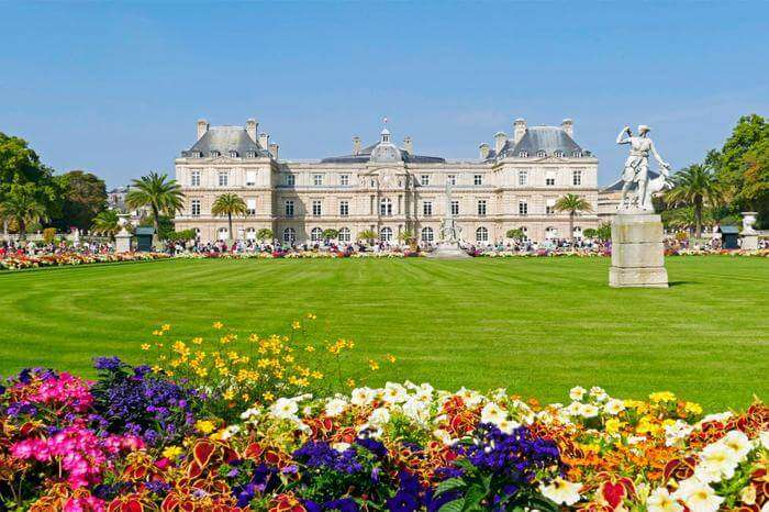 a grand palace in garden surrounded by flowers