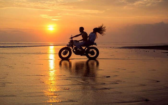 A couple biking on a beach in Bali
