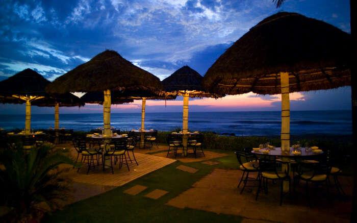 Romantic dining setup below huts by the sea beach at Bay View in Vivanta in Chennai