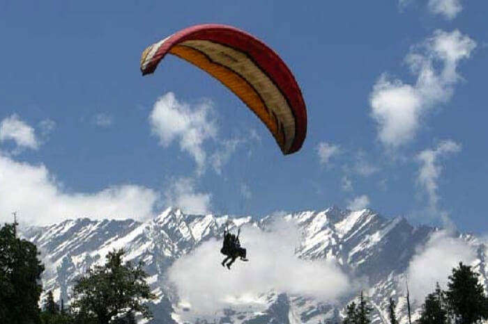 A traveler paragliding in Solang Valley in Manali