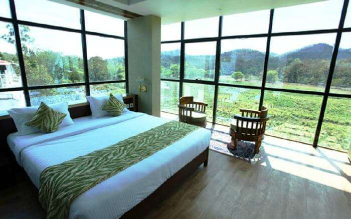 glass wall hotel room with mountain views at Hotel Tiger Roare