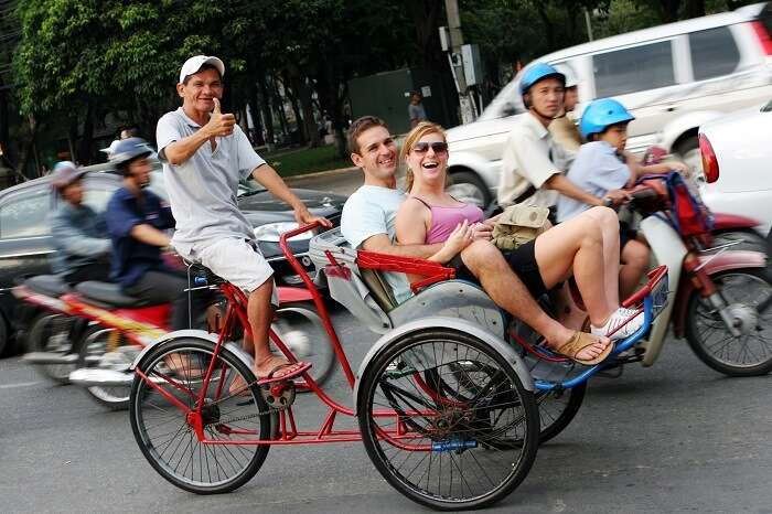 A couple taking a city tour in a cyclo in Hanoi