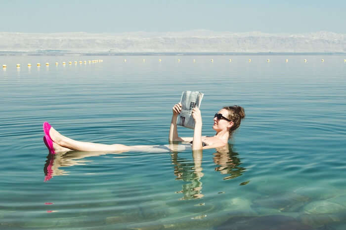 A woman reading newspapaer while floating in the Dead Sea