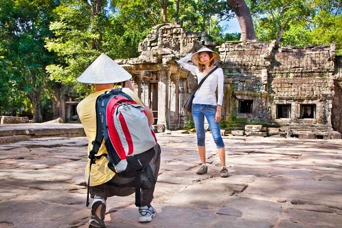 Beautiful young couple at Prasat Ta Prum or Ta Prohm Temple complex in Siem Reap