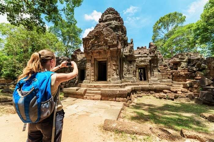 Young female tourist with smartphone taking picture of the gopura under blue sky near the entrance to ancient Preah Khan temple in Angkor