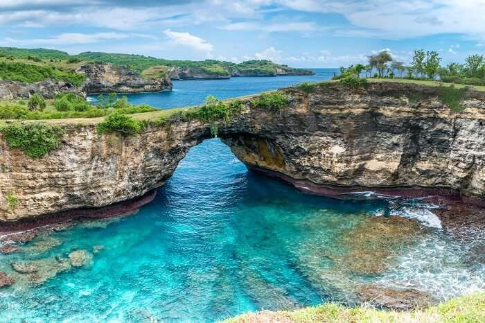 Stone arch over the sea at the rocky coastline on Nusa Penida island near Bali in Indonesia