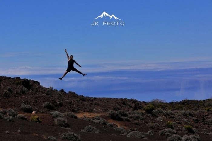 man jumps near a volcano in Reunion Island, France