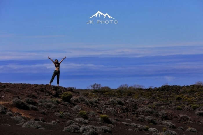 female jumps near a volcano in Reunion Island, France