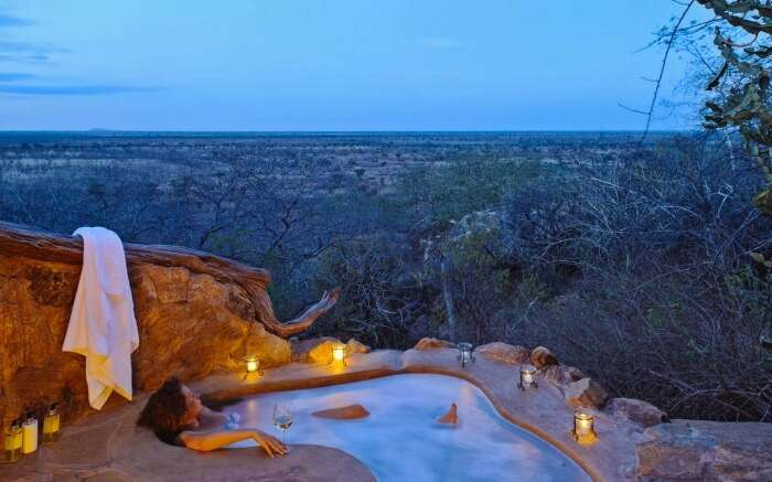 A woman in an outdoor jacuzzi in a honeymoon lodge in South Africa