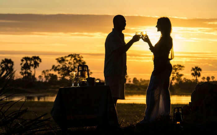 Couple raising a toast during their honeymoon in Botswana