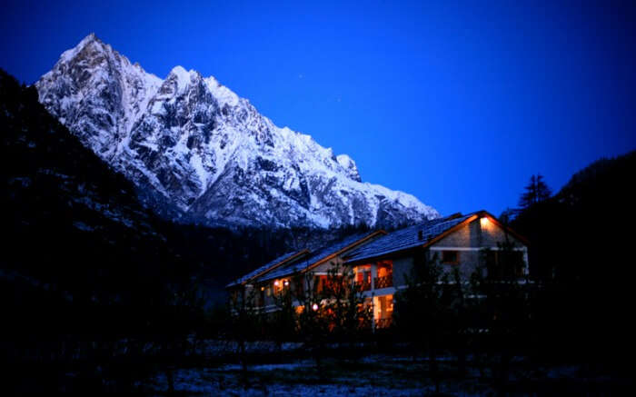Night view of Banjara Retreat in Sangla overlooking snow clad peaks
