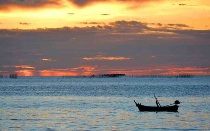 a boat against the orange sunset sky at Naklua beach