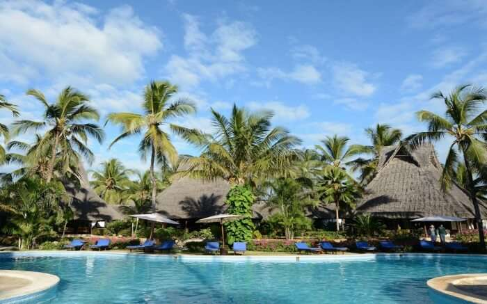 an open pool surrounded by palm trees in a Zanzibari thatched roof resort