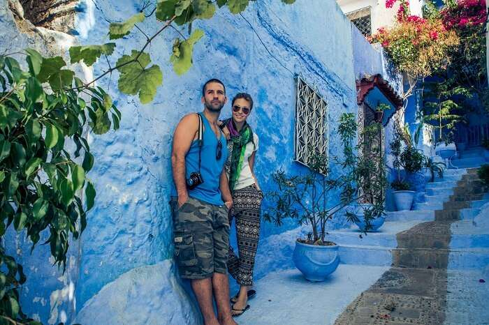 A couple posing in the blue town of Chefchaouen in Morocco