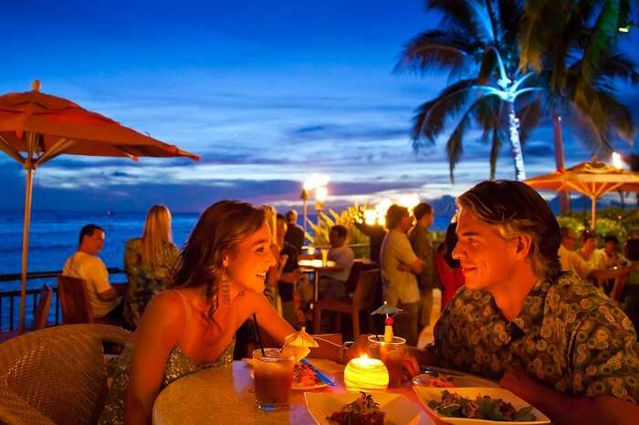 A couple enjoying a romantic candle-lit dinner in Hawaii
