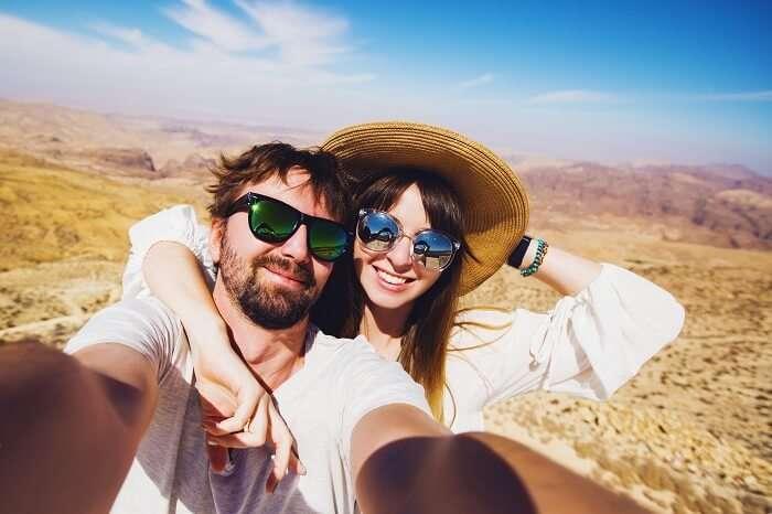 Young travel couple taking selfie after a trek on their Jordan honeymoon