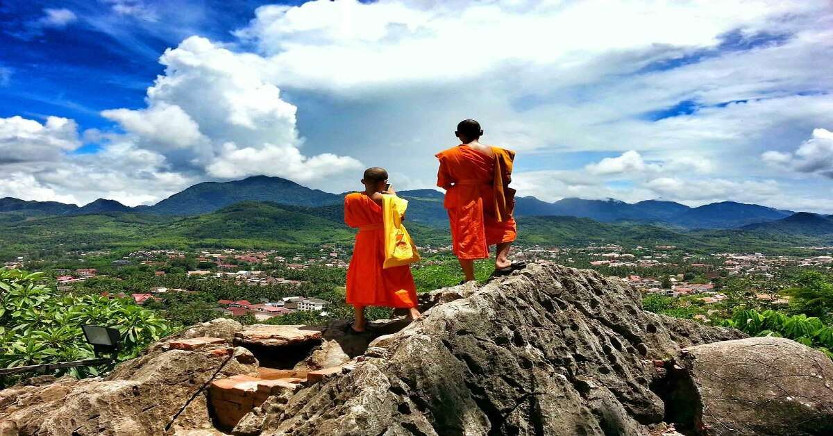 two Buddhist monks standing on a hill