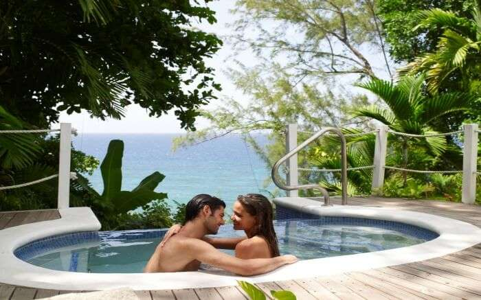 A couple in a pool overlooking Caribbean Sea