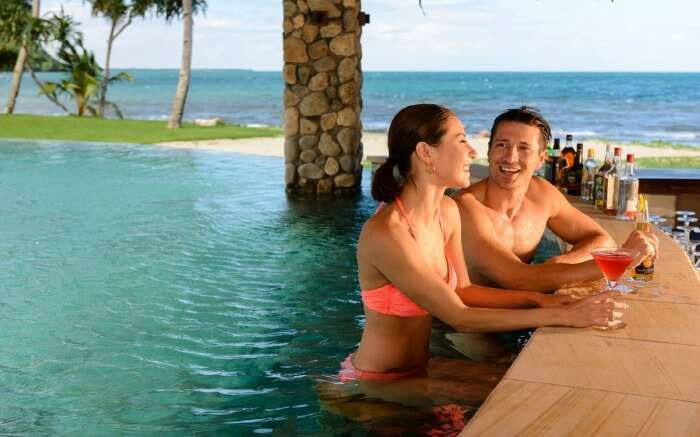 A couple relaxing on a beach by the ocean in Nanuku Resort and Spa in Fiji
