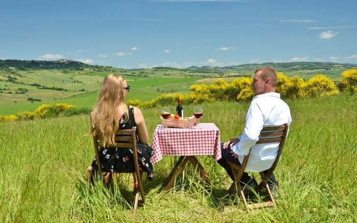 A couple sitting amid fields of Tuscany