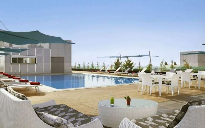 A pool on terrace with sitting area in a resort in Amman