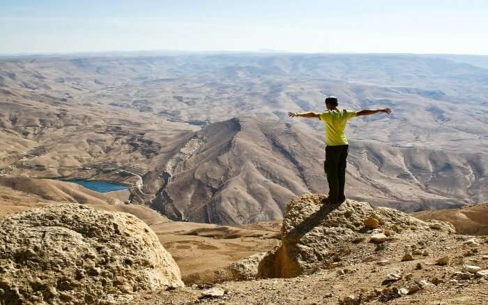 A tourists standing at the edge of a cliff in the mountains of Jordan