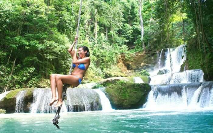 A woman swinging on a rope in Black River