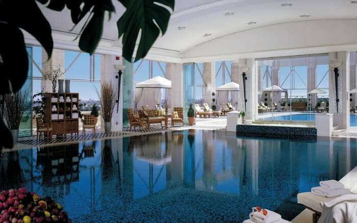 An indoor pool with sundecks and cabanas around