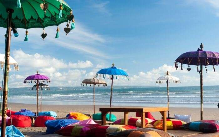 Colourful bean bags with a wooden table on Kuta beach
