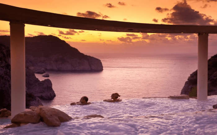 Couple spending leisure moments in an infinity pool at the time of sunset in Spain