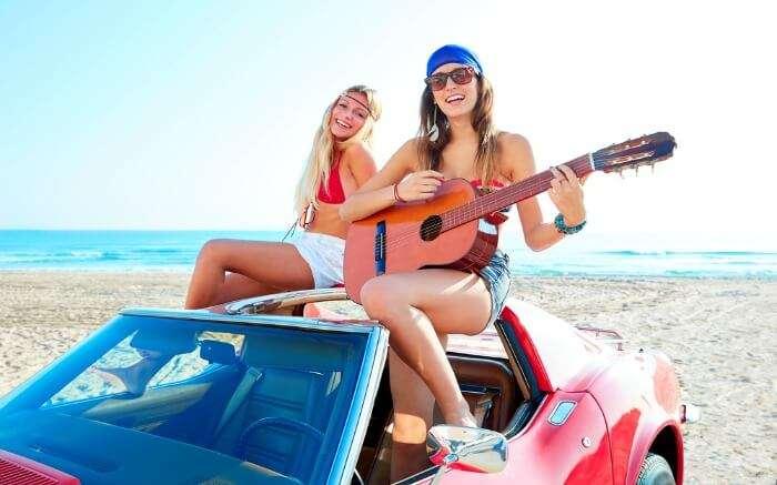 Girls on a beach having fun with guitar