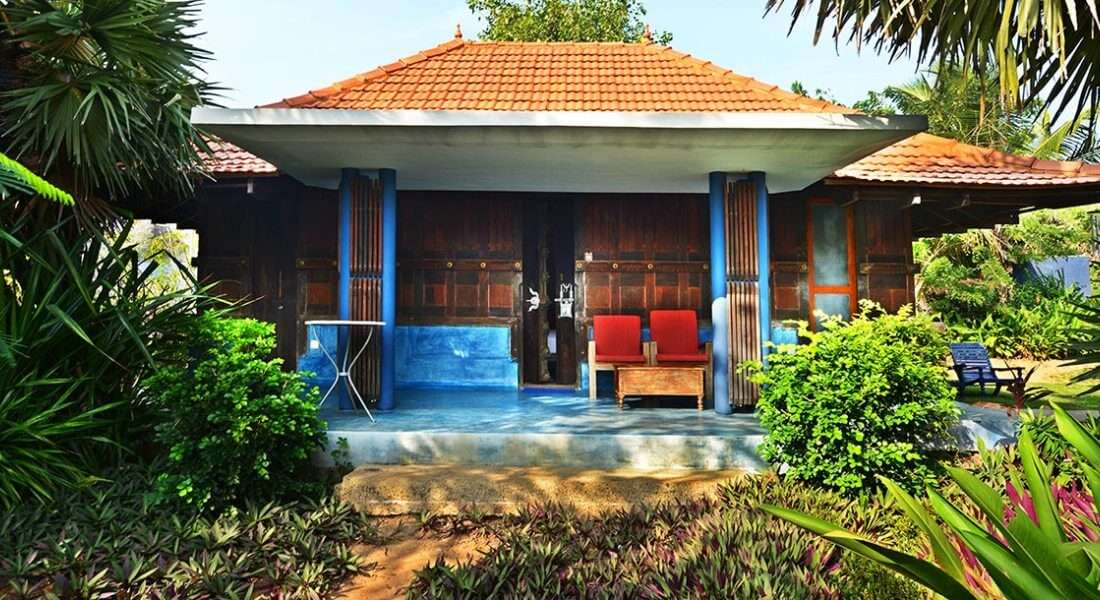 A south Indian style cottage surrounded by palms