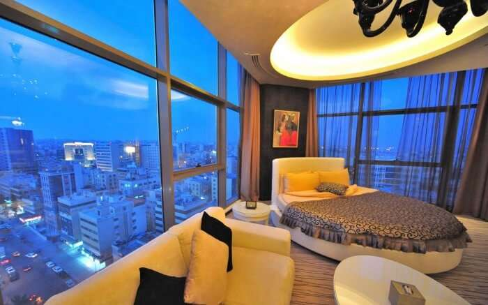 a hotel room with a bed and city view