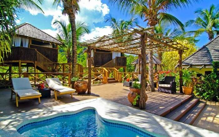 a small outdoor pool with two cabanas under the shade of palm trees