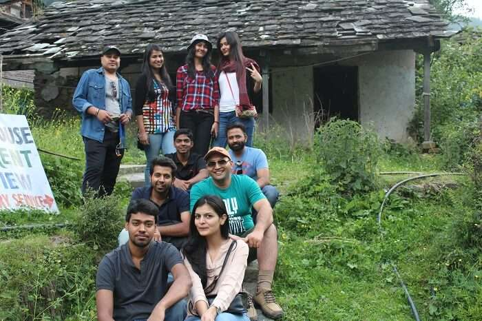 A bunch of travelers relaxing outside a rustic hut in Kasol